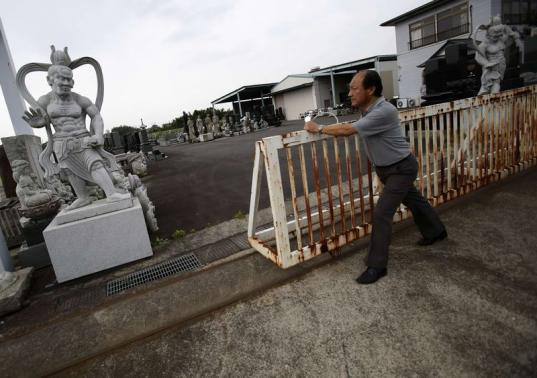 An Jianxing, a 50 year old gravestone business owner and designer, closes the gate of his company showroom in Ibaraki prefecture, north of Tokyo September 10, 2014.  CREDIT: REUTERS/YUYA SHINO